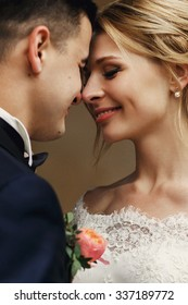 Happy sensual handsome groom and blonde beautiful bride in white dress hugging  close-up