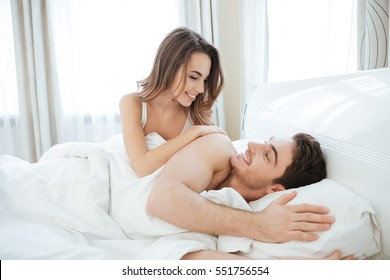 Happy sensual young couple lying in bed together in the morning