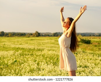 Happy  and serene behavior woman  outdoor with raised hands. Young cheerful girl is on nature over the spring field. Happiness . Freedom concept. Pretty and joyful  model is relaxing on meadow