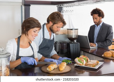 Happy servers preparing sandwiches together at the coffee shop