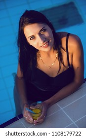 Happy sexy woman with juice in swimming pool.