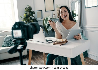 Happy to share her ideas. Beautiful young woman gesturing and smiling while making new video for her blog