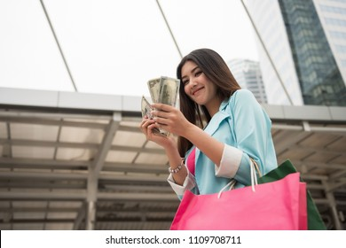 Happy shopaholic Asian girl counting dollar bills in hands.  discount or Black Friday sale with modern city background.