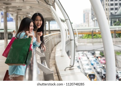 Happy shopaholic friends look for shopping mall in town. Two beautiful young Asian women enjoying summer discount sale at modern city. Foreign travellers.