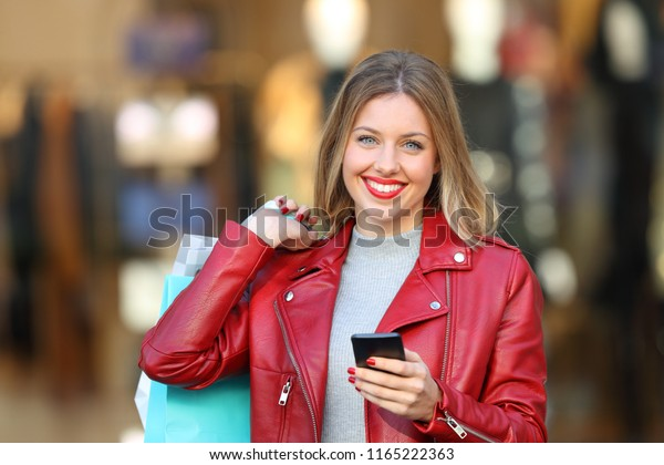Happy shopper posing holding a smart phone and shopping bags in the street with a storefront in the background