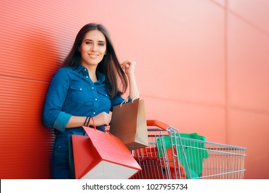 Happy Shopper Woman with Shopping Cart in front of Store. Smiling girl with pushcart and gift bags near shop