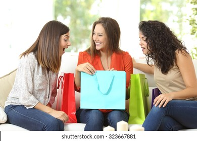Happy shoppers with shopping bags talking sitting on a couch at home