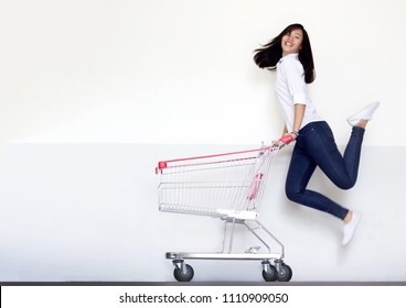 happy shopping asian girl jumping with shopping cart on white background. Shopping girl with casual suite portrait action model for marketing concept.