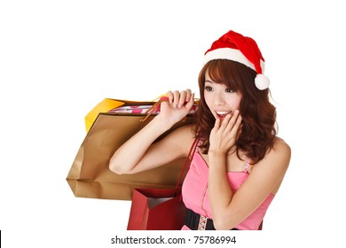 Happy shopping girl holding bags and wearing Christmas hat with surprised expression, half length closeup portrait on white background.
