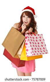 Happy shopping girl holding bags and wearing Christmas hat, half length closeup portrait on white background.