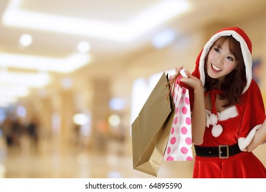 Happy shopping girl wearing Christmas clothes holding bags in department store.