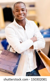 Happy shopping man holding bag at the mall and smiling