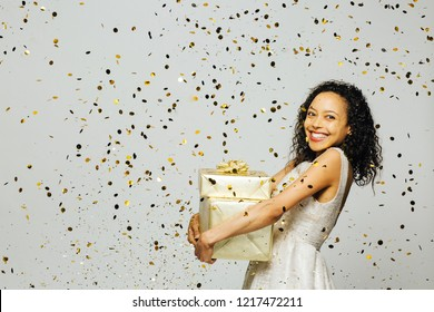 Happy shopping for presents,  portrait of a woman in a white dress with a big smile holding gifts as gold confetti are falling