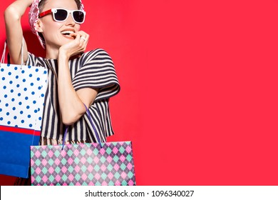 Happy shopping woman  with shopping bags over bright red background wearing hat and sunglasses
