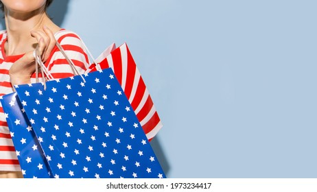 Happy shopping woman with shopping bags over blue background wearing striped clothing and shoping bags in patriotic colors