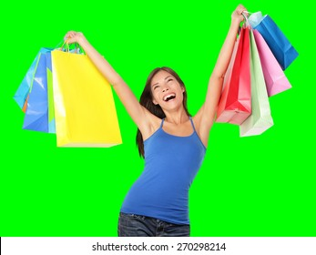 Happy shopping woman excited and cheerful in joyful bliss. Shopper holding colorful shopping bags isolated on green screen chroma key background. Elated beautiful Caucasian Asian Chinese female model.