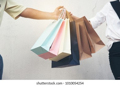 Happy shopping woman hold shopping bags on the street with her boyfriend. She  enjoy in lifestyle shopping concept, in midnight sales and discount on sales.