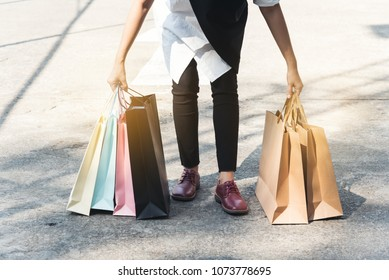 Happy shopping woman hold shopping bags on the street. She  enjoy in lifestyle shopping concept, in midnight sales and discount on sales.