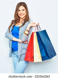 Happy shopping woman holding paper bag. Smiling girl portrait on white background. Young female model one in studio.