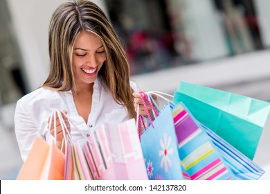 Happy shopping woman looking at purchases and smiling