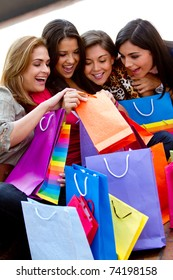 Happy shopping women looking into bags and smiling
