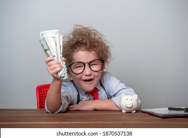 Happy shouting kid with money dollars cash in hand. Education for child how to be rich. Little millionaire. Child at table with bills