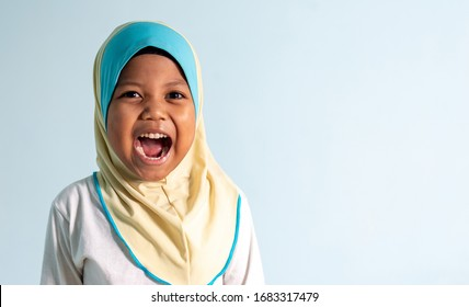 Happy and shouting Muslim girl wearing hijab isolated portrait.  Shallow depth of field