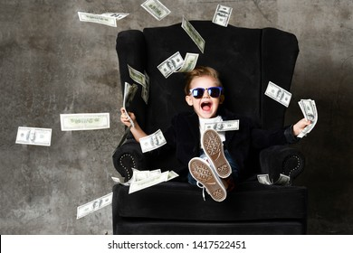 Happy shouting self-confident rich kid boy millionaire sitting with legs crossed in luxury armchair and throwing money dollars cash. Overspend.