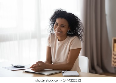Happy shy young african american woman laughing sitting at home office desk, cheerful millennial black girl student entrepreneur smiling relaxing having fun finish work or study at table