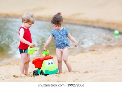 Happy siblings: boy and girl playing together in summer.