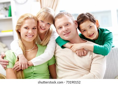 Happy siblings embracing their parents at home