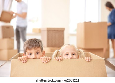Happy siblings hiding inside box in their new home