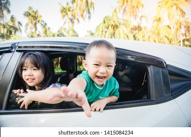 Happy siblings laughing and smiling near window go travel by car against blue sky and coconut trees.Summer road trip, Family with children in car.