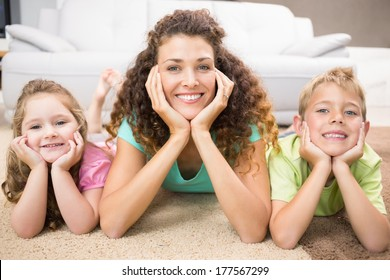 Happy siblings lying on the rug posing with their mother at home in living room