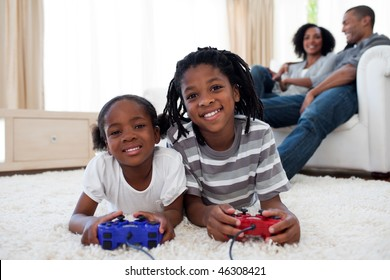 Happy siblings playing video game lying on the floor