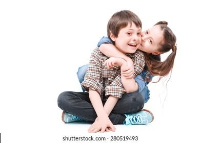 Happy siblings. Portrait of a small handsome boy sitting on the floor with his legs crossed and his small sister sitting behind him hugging and kissing his cheek isolated on white background