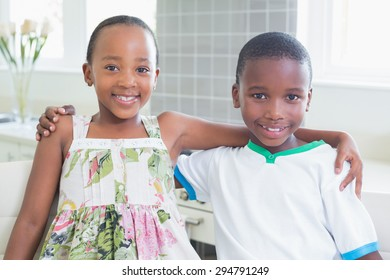 Happy siblings smiling at camera at home in the kitchen
