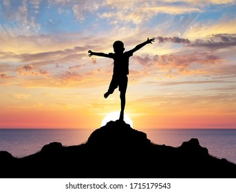 Happy silhouette of boy enjoy the nature. Spread arms to the sun and deep sky. Emotional and coceptual scene.