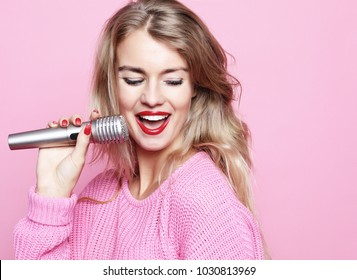 Happy singing girl. Beauty woman wearing pink pullover  with mic