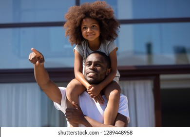 Happy single african dad holding cute kid daughter on shoulders outdoors looking forward showing good future vision playing outside, little child girl embracing loving black father dreaming together