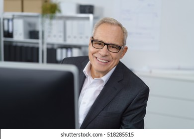Happy single man behind computer screen at small office with bookshelf in background