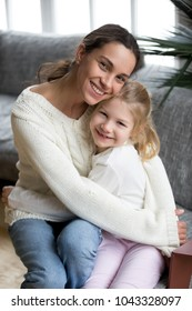 Happy single mother embracing cute little adopted girl looking at camera, smiling cheerful mom hugging preschool daughter at home, young diverse mommy and kid bonding cuddling, vertical portrait
