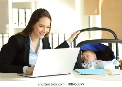 Happy single mother working on line and taking care of her baby at office