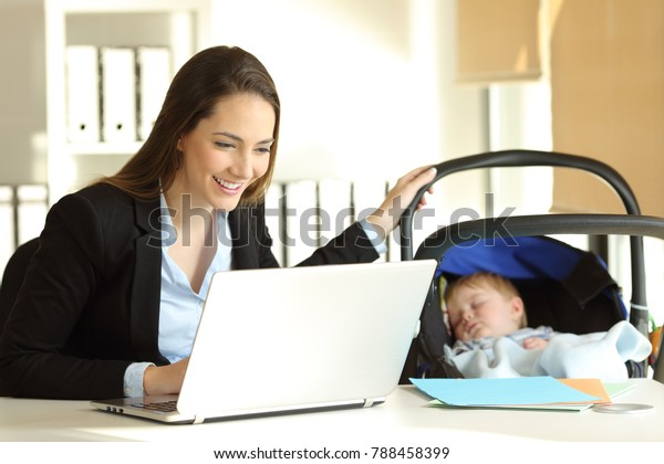 Happy alleinerziehende Mutter, die online arbeitet und ihr Baby im Büro pflegt