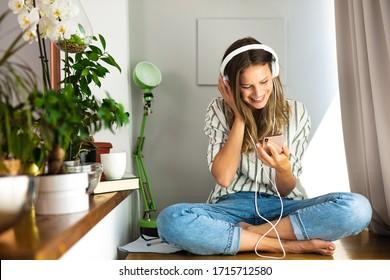 Eine glückliche Einzelfrau, die Musik auf dem Schreibtisch neben den Pflanzen und dem hellen Fenster hört, von zu Hause aus arbeitet, zu Hause bleibt.