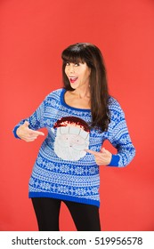 Happy single woman pointing to her ugly blue sweater with Santa Claus face on it