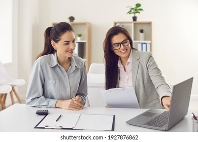 Happy single young business woman consulting bank manager, financial advisor or loan broker. Smiling estate agent meeting client at office, talking, showing and offering house design options on laptop - Shutterstock ID 1927876862