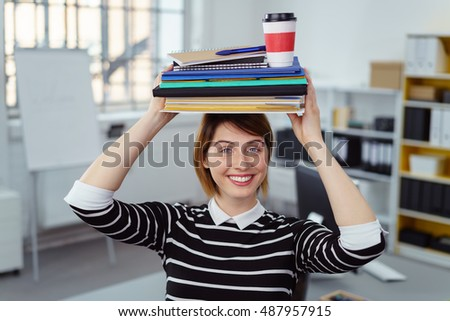 Happy Single Young Woman Balancing Notebooks And Drink On Head In Small Office With Bookshelf