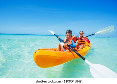 Happy sister and brother kayaking at tropical sea on yellow kayak