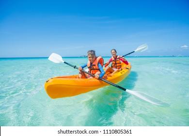 Happy sister and brother kayaking at tropical sea on yellow kayak